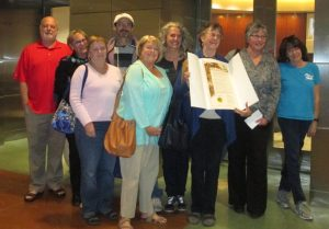 Photo of supporters with certificate